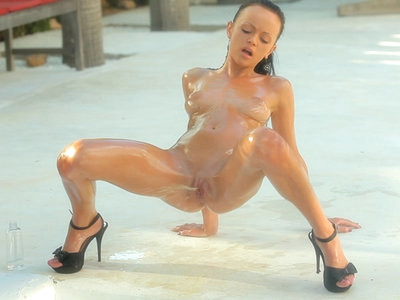 Oiled nymph pees outdoors