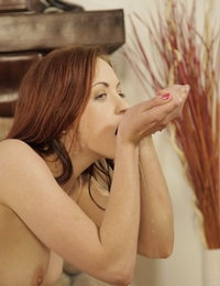 Sexy redhead toys her piss soaked pussy with a dildo